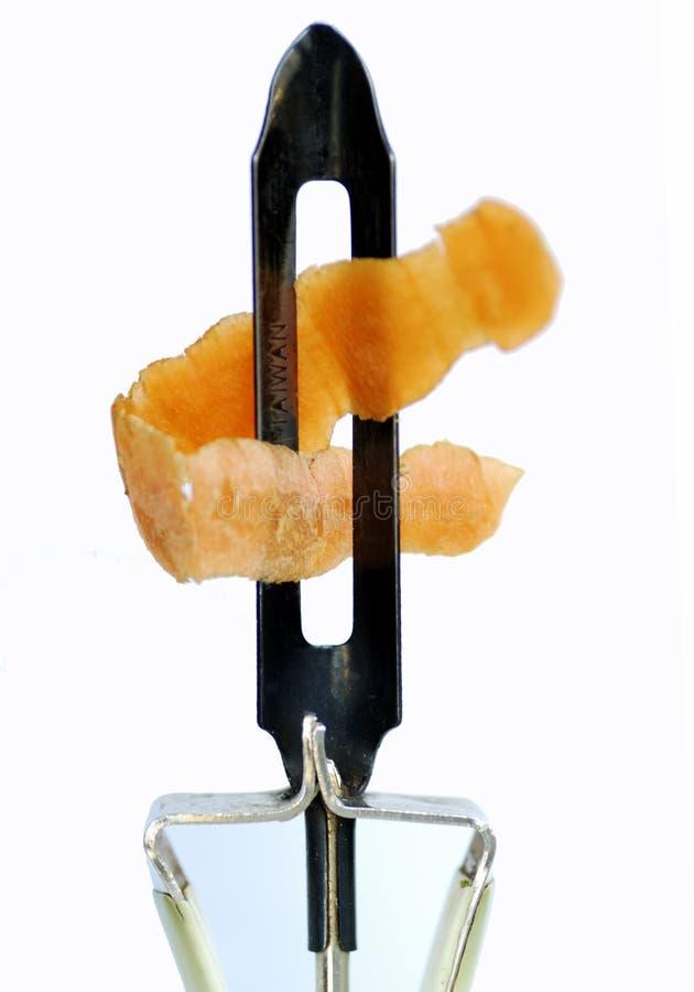 Unter Verwendung des Karotteschälers, zum der Karottehaut zu löschen lizenzfreie stockbilder
