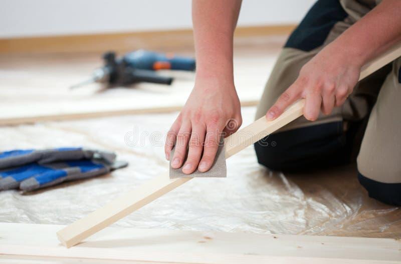 Unter Verwendung des Sandpapiers für das Polieren der hölzernen Planke stockbild