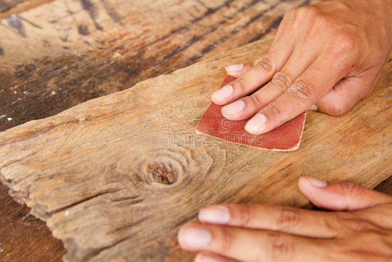 Unter Verwendung des Sandpapiers scheuern Sie Planke hölzern für die Herstellung der Tabelle, Möbel lizenzfreies stockbild