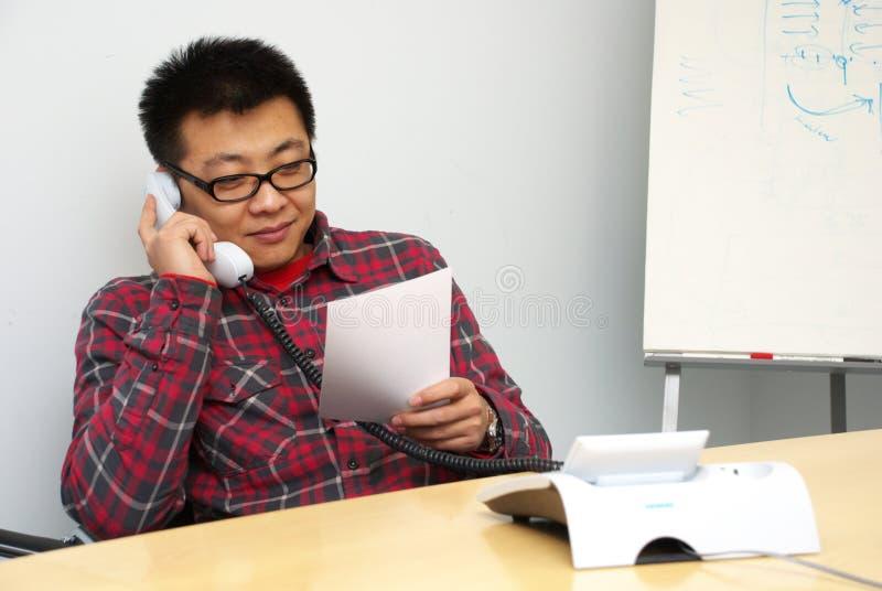 Unter Verwendung des Telefons im Büro stockfotos