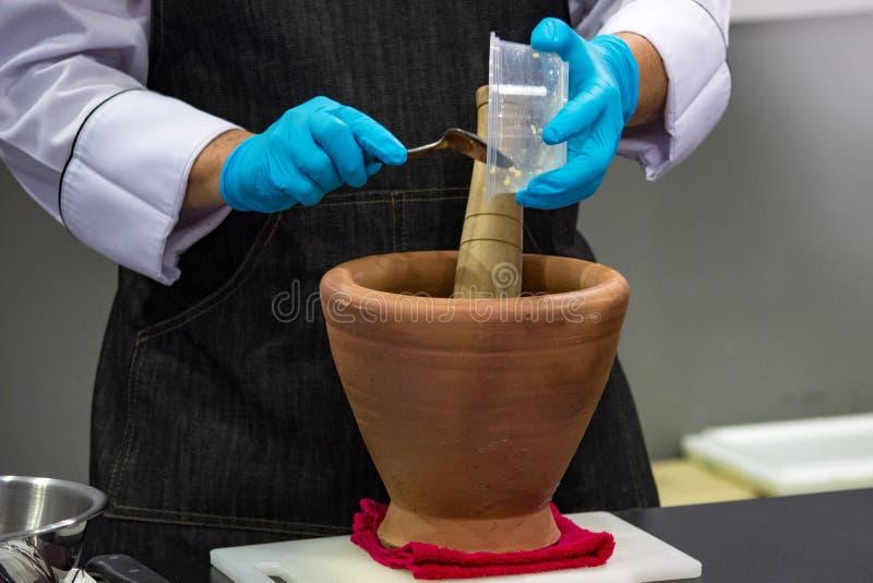 Unter Verwendung eines Mörsers und einer Stampfe, zum von Bestandteilen für thailändische Nahrung zu zerstoßen, Pfundmörser stockbild