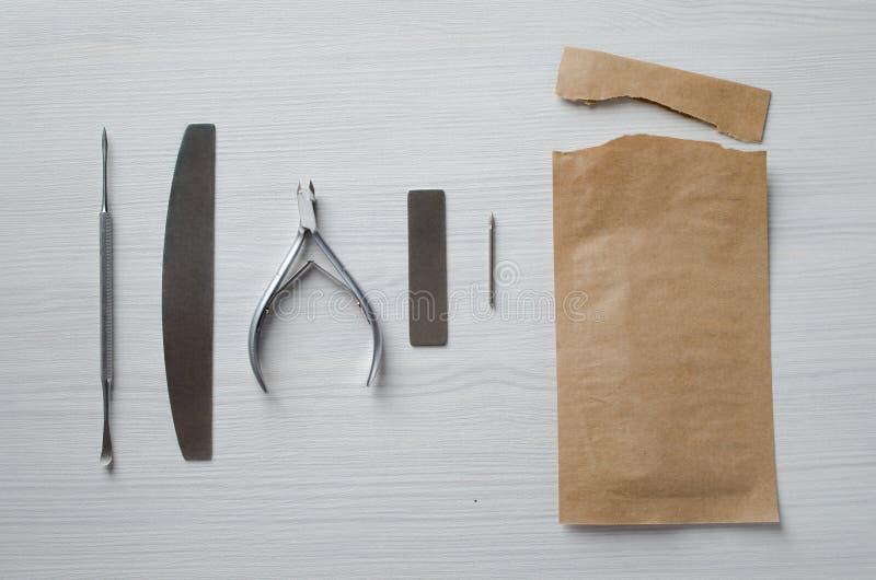 Unter Verwendung Kraftpapier-Taschen f?r Sterilisierungsmanik?rewerkzeuge stockfotos