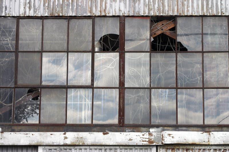 Unterbrochene Fenster an verlassenem Fabrikgebäude lizenzfreies stockbild