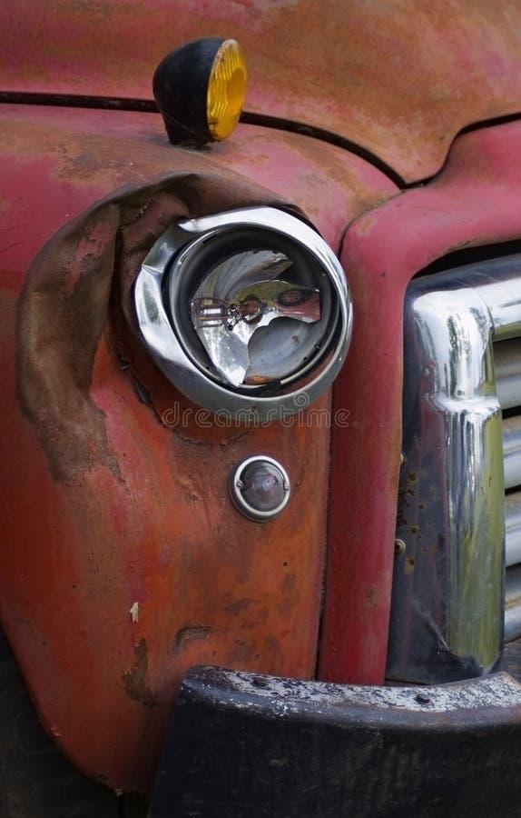 Unterbrochener Scheinwerfer auf altem rotem LKW lizenzfreie stockfotografie