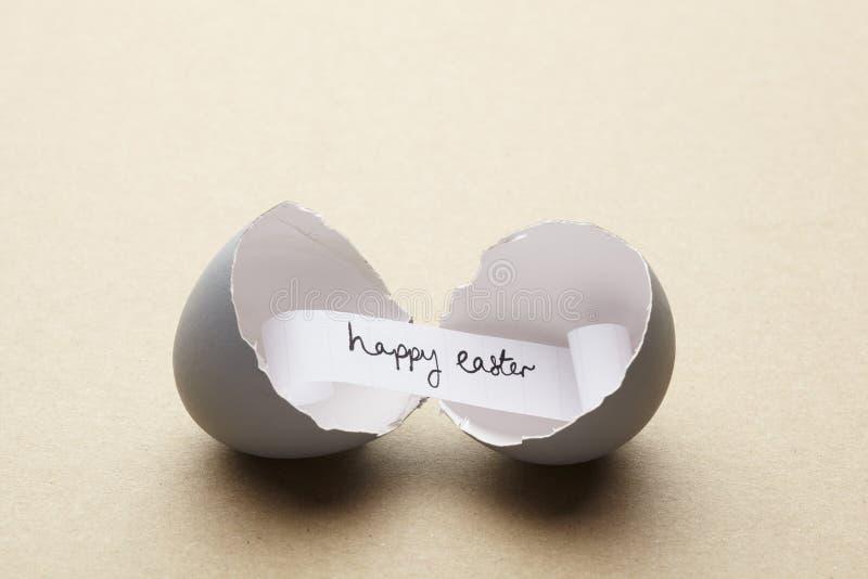 Unterbrochenes offenes Ei mit glücklicher Ostern-Meldung nach innen stockfoto