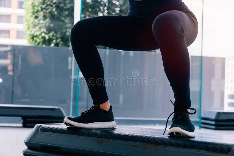 Unterer Teil der Eignungsfrau in der Sportkleidung, die tiefe Hocke an der Turnhalle tut lizenzfreies stockfoto