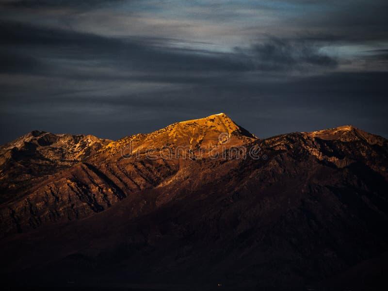 Untergehende Sonne reflektiert goldenes orange Licht auf die Oberseiten der Bergspitzen in Utah lizenzfreie stockbilder