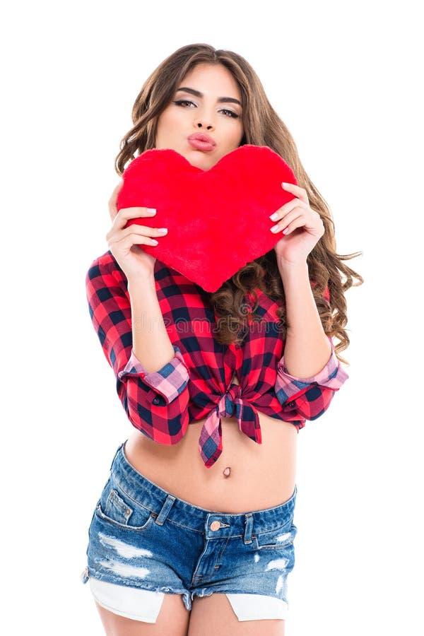 Unterhaltende Frau, die rotes Herz hält und lustiges Entengesicht macht lizenzfreie stockbilder
