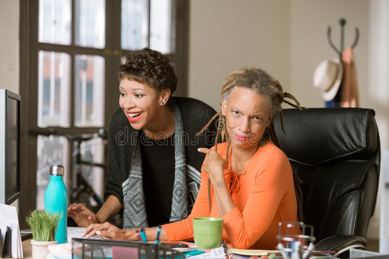 Unterhaltene Frau, die zum ?ppigen Mitarbeiter reagiert stockbilder