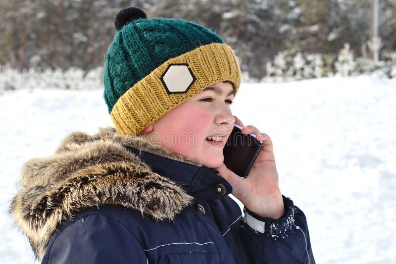 Unterhaltung auf dem Telefonjungen in einer Strickmütze mit einer Bubo- und Pelzhaube auf einem Winterweg lizenzfreies stockbild
