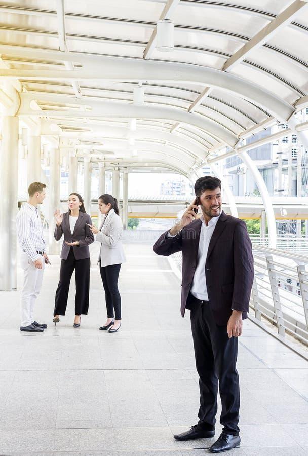 Unterhaltung mit Freunden Hübscher Geschäftsmann, der am Handy spricht und mit seinem Freundplaudern lächelt lizenzfreies stockbild