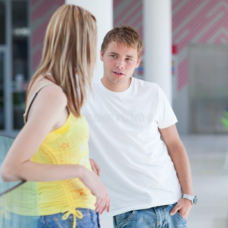 Unterhaltung mit zwei Studenten/, die auf Campus flirtet stockfoto