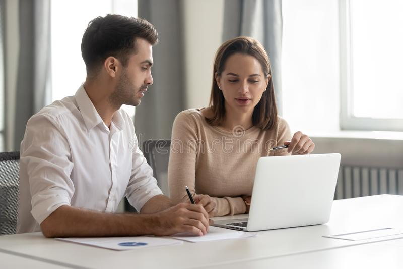 Unterhaltungsunterrichtender männlicher Kollegeinternierter des weiblichen Mentors, der Laptop betrachtet stockfotos