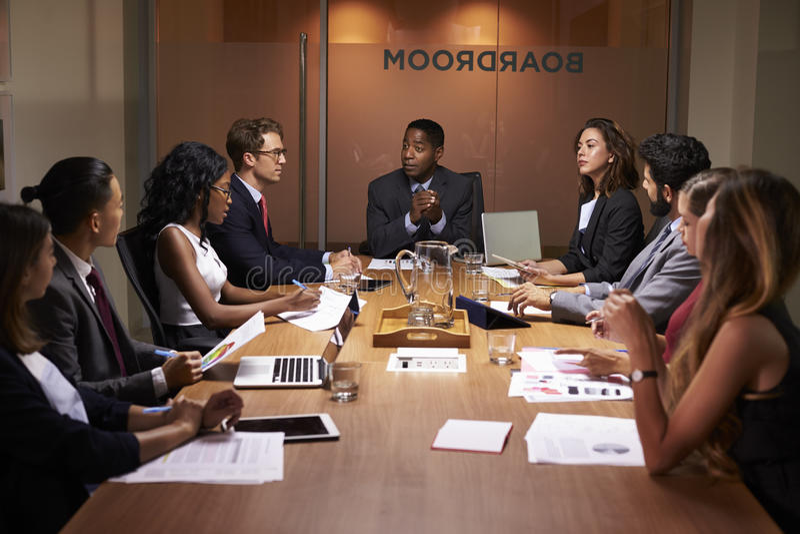 Unternehmensgeschäftsleute bei einer Abendsitzungssaalsitzung lizenzfreie stockbilder