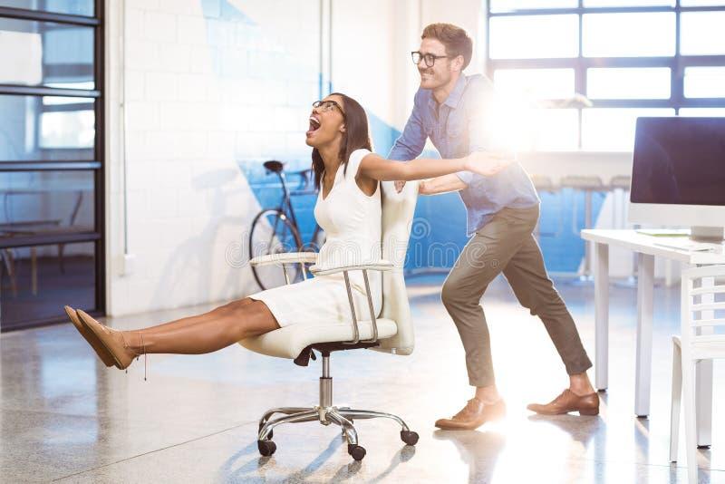 Unternehmensleiter, der Geschäftsfrau im Bürostuhl drückt stockfotografie