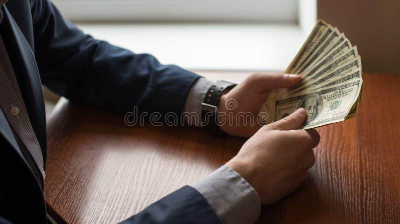 Unternehmensleiter im Gesellschaftsanzug, der Geld als Bestechungsgeld gibt Mann in der Klage stockbild