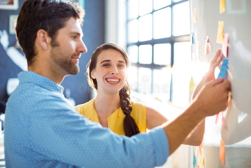 Unternehmensleiter und Mitarbeiter, die klebrige Anmerkungen auf whiteboard setzen lizenzfreies stockbild