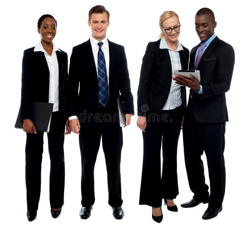 Unternehmensteam von vier aufwerfend mit Tablette-PC lizenzfreie stockbilder