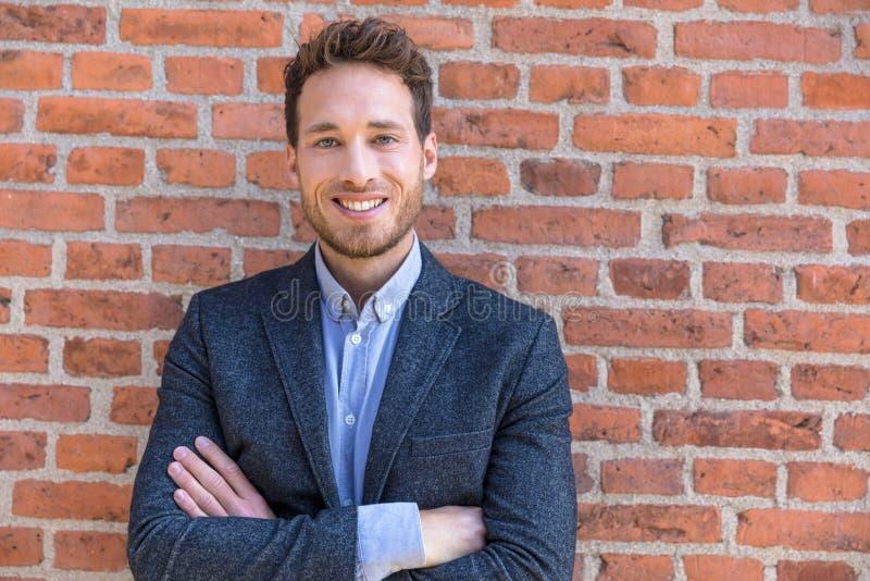 Unternehmermann des Geschäftsmannporträts überzeugter junger, der Kamera gegen städtische Backsteinmauerbeschaffenheit betrachtet lizenzfreie stockfotos