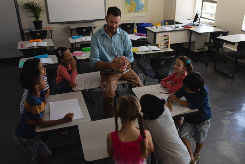 Unterricht des männlichen Lehrers im Klassenzimmer der Volksschule stockfotos
