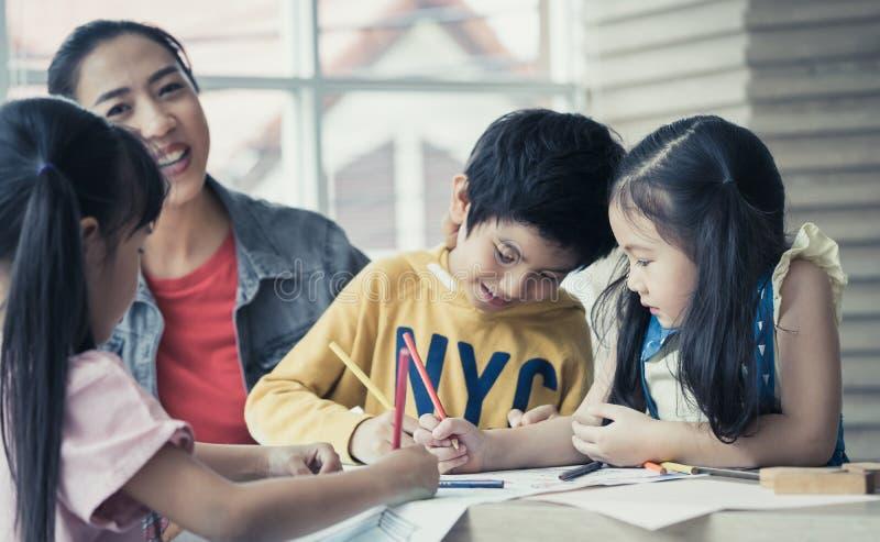 Unterrichtende Kinder des asiatischen Lehrers im Kindergartenkunstklassenzimmer stockfotografie