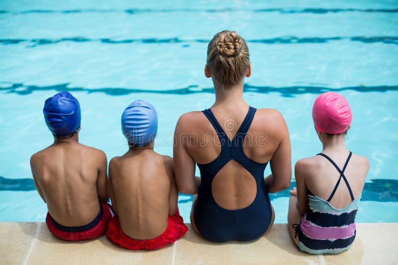 Unterrichtende Kinder des weiblichen Lehrers am Poolside stockbilder