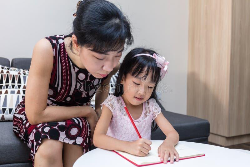 Unterrichtende Tochter der asiatischen chinesischen Mutter, die Hausarbeit tut lizenzfreie stockbilder