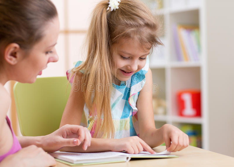 Unterrichtende Tochter der Mutter Kinderzu lesen lizenzfreie stockfotografie
