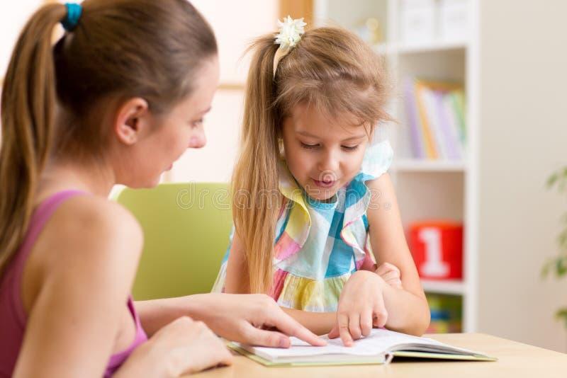 Unterrichtende Tochter der Mutter Kinderzum Ablesen stockbilder