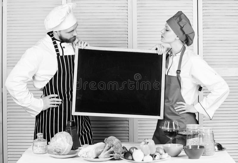Unterrichtende verschiedene kochende Techniken Paare des Mann- und Frauenholdingbrettes, wenn Schule gekocht wird Vorlagenkoch un stockbilder