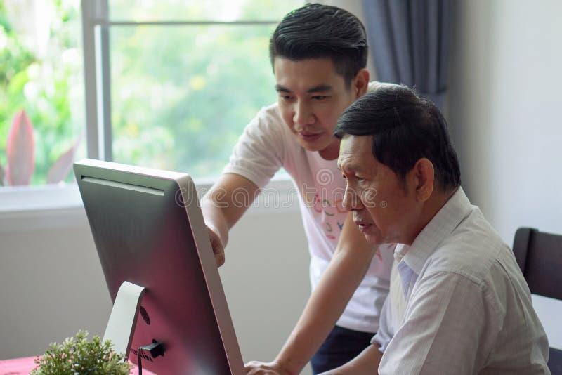 Unterrichtender Großvater des Enkels wie zum Einsetzen des Computers und der Technologie im Haus junge Lehrerhilfenälterer Mann,  stockfoto