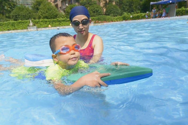 Unterrichtender Sohn der Mutter lernen, im Sommer zu schwimmen stockbild