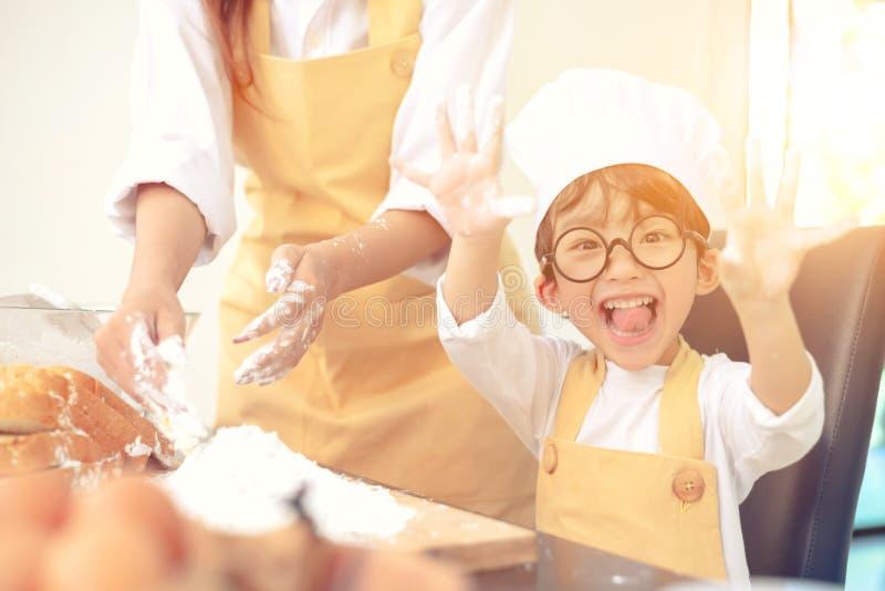 Unterrichtendes Kind der Mutter für Kochnahrung Vorbereiten eines Bestandteiles lizenzfreies stockfoto