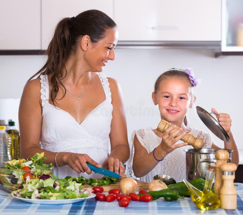 Unterrichtendes Mädchen der Frau zu kochen lizenzfreies stockbild