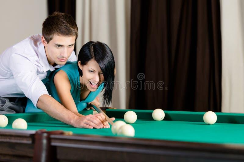 Unterrichtendes Mädchen des Mannes, zum von Billard zu spielen lizenzfreies stockbild