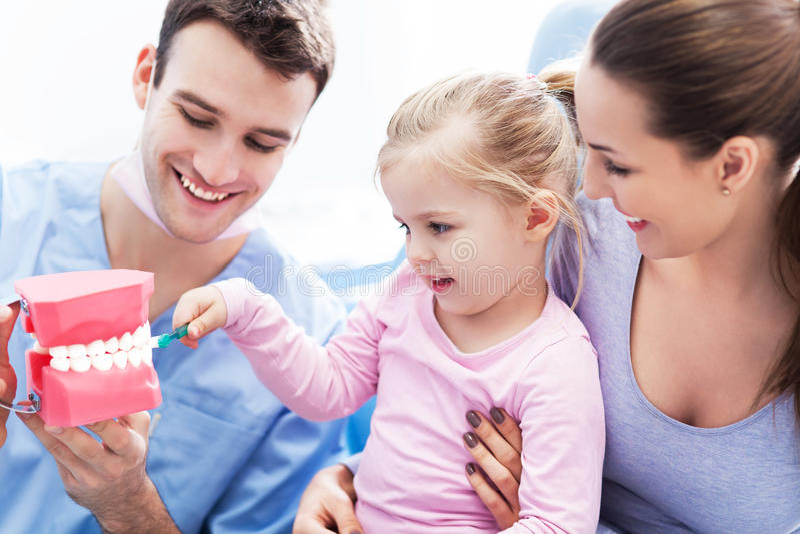 Unterrichtendes Mädchen des Zahnarztes, wie man Zähne putzt lizenzfreie stockfotografie