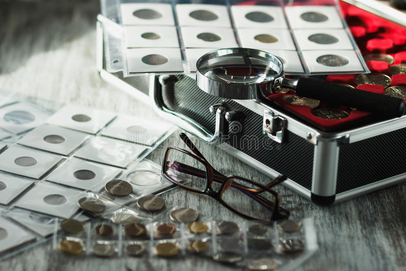 Unterschiedliche alte Münzen, Gläser und Lupe, Weichzeichnungshintergrund lizenzfreie stockfotografie