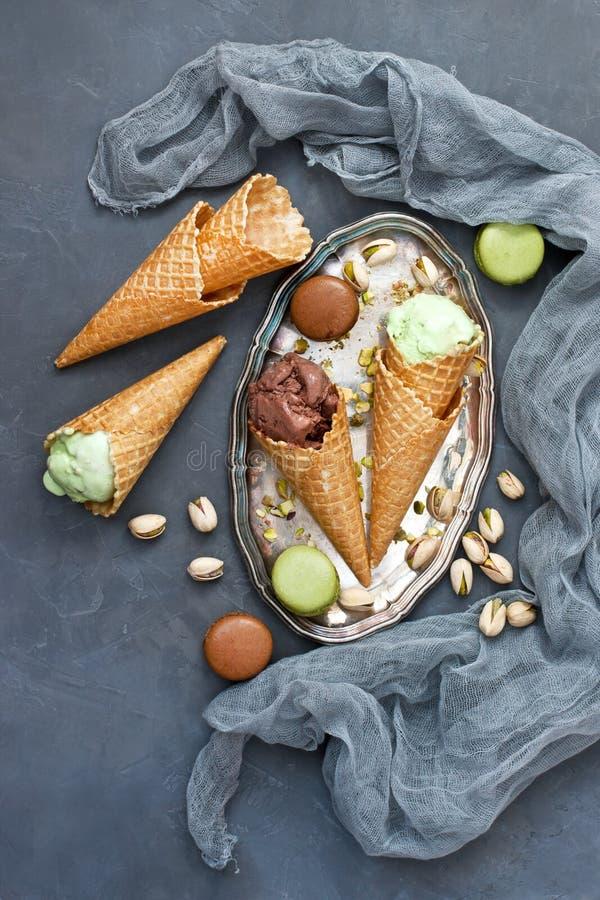 Unterschiedliche Art der Eiscreme in den Waffeln und in macarons Pl?tzchen auf konkretem Hintergrund lizenzfreie stockbilder