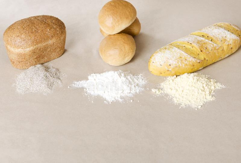Unterschiedliche Art des Mehls und der Laibe des Brotes auf dem Papierhintergrund lizenzfreies stockfoto