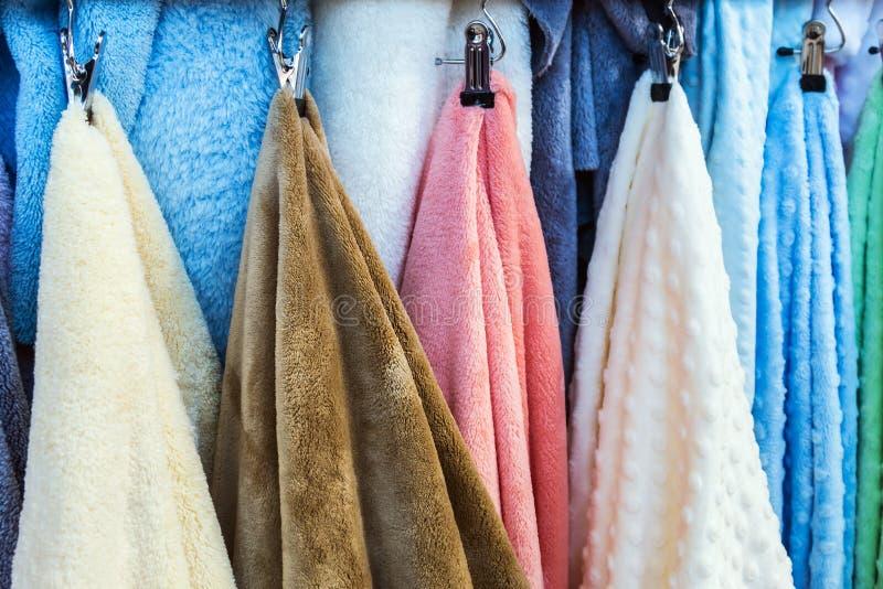 Unterschiedliche Farbgroße Badetücher auf dem Raum des Aufhängers unter der Dusche lizenzfreies stockbild