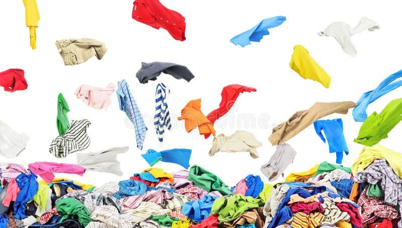 Unterschiedliche Kleidung, die am großen Stapel von Kleidung auf einem Weiß fällt lizenzfreies stockfoto