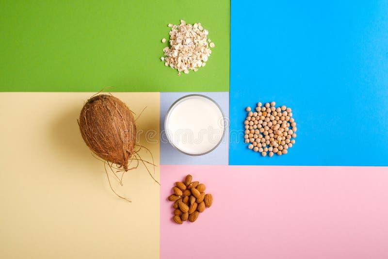 Unterschiedliche Molkereifreie Milchbestandteile Kokosnuss, Hafersommersprossen, Soja, Mandelnüsse auf mehrfarbigem Hintergrund A lizenzfreies stockbild