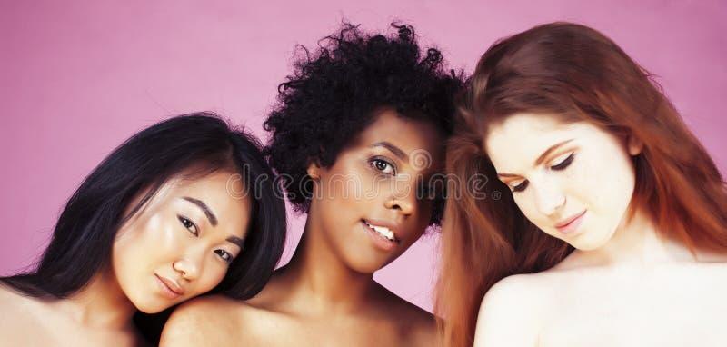 Unterschiedliche Nation: afrikanisch-amerikanisch, kaukasisch, asiatisch auf rosafarbenem Hintergrund glücklich lächelnd, vielfäl stockbild