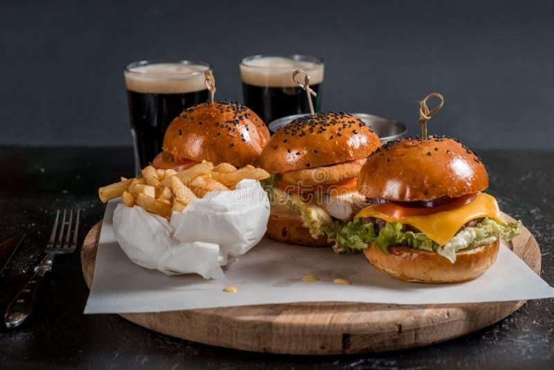 Unterschiedlicher Burger drei auf enormem hölzernem Brett mit Essiggurken, Ketschup, Majonäse, Fischrogen und hellem Bier, Draufs lizenzfreies stockfoto