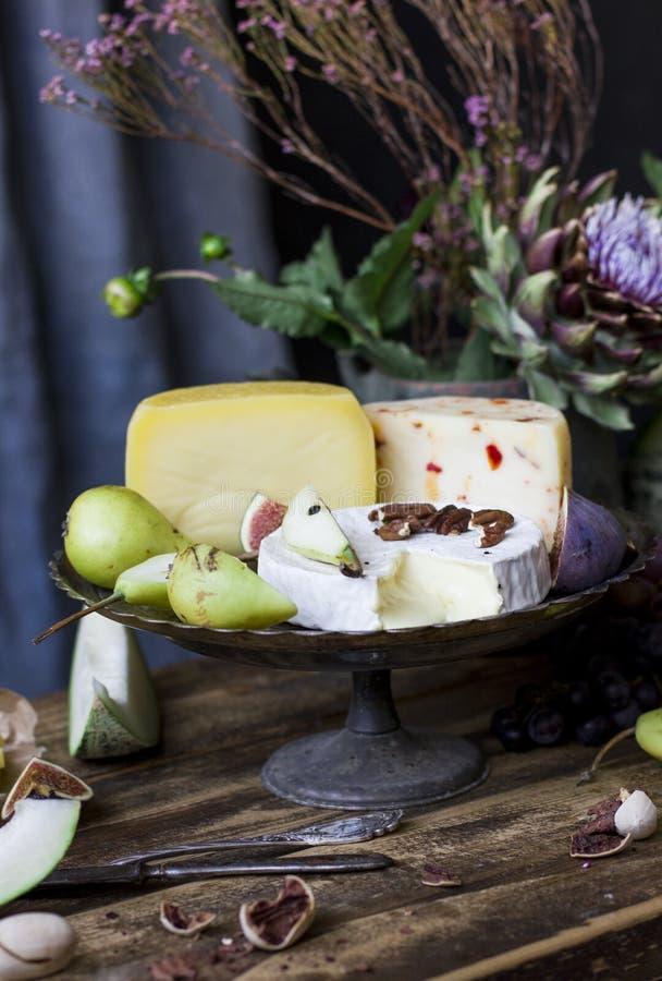 Unterschiedlicher Käse, frische Frucht und Gartenblumen auf dem alten Holz stockbilder
