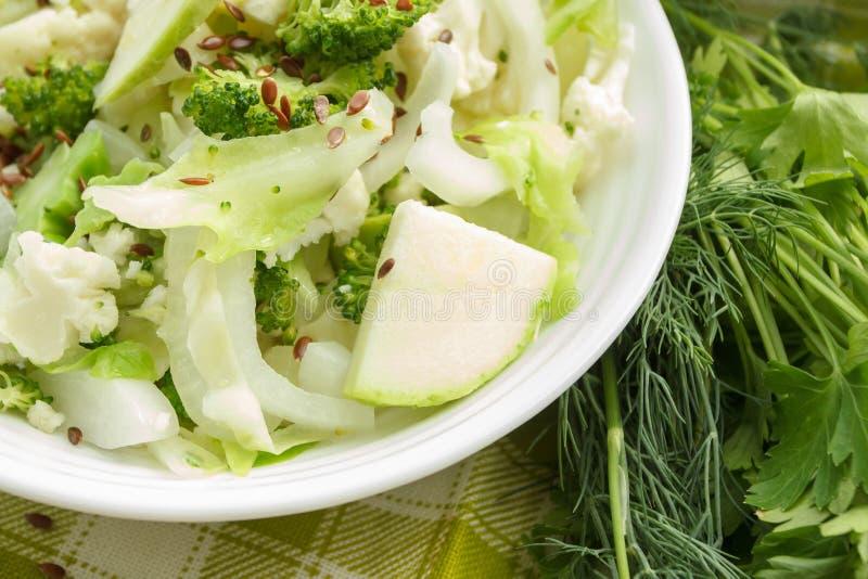 Unterschiedliches grünes und weißes, frisches, rohes Gemüse in der weißen Schüssel mit Leinsamen stockfotografie