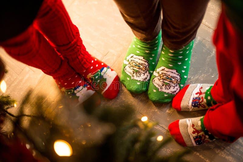 Unterseite für Auslegung Drei Paare des Fußes, gekleidet in Weihnachts-soks, stehen um einen Baum Atmosphäre von Weihnachten stockbilder