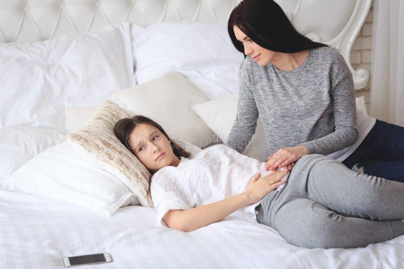 Unterstützende Mutter, die ihrer besorgten jugendlichen Tochter hilft stockfotos