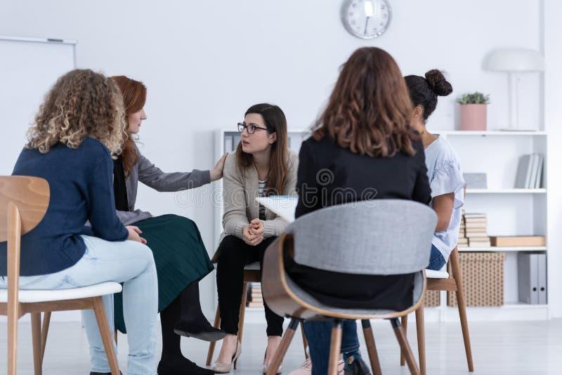 Unterstützungsfreund der Rothaarigefrau während der Psychotherapiegruppensitzung stockfoto