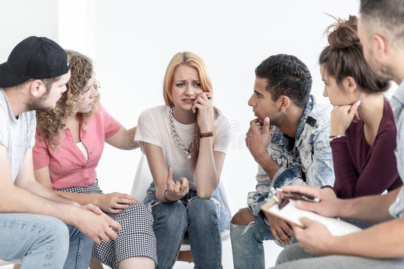 Unterstützungsschreiende Jugendliche der jungen Leute während der Sitzung mit Therapeuten lizenzfreie stockbilder
